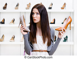 Woman can't choose pumps - Woman keeps two pumps in the...