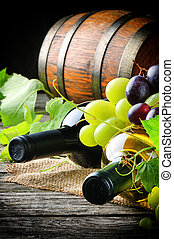 Bottles of red and white wine with fresh grape and wooden...
