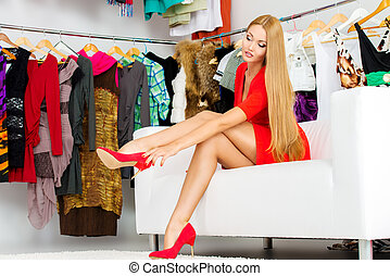 shoes and clothes - Fashionable girl choosing shoes in a...