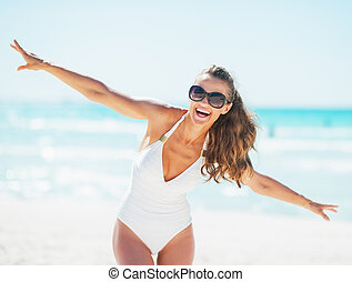 Happy young woman in swimsuit having fun time on beach