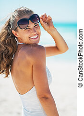 Portrait of smiling young woman in swimsuit with sunglasses...