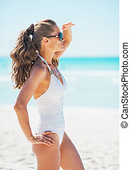Young woman in swimsuit and sunglasses on beach looking into...