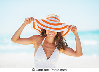 Portrait of smiling young woman in swimsuit hiding behind...
