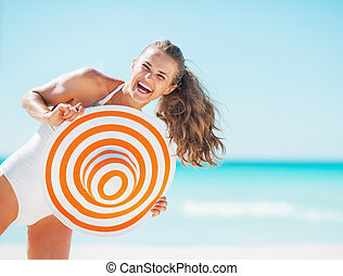 Portrait of happy young woman in swimsuit with beach hat...