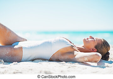 Happy young woman in swimsuit tanning on beach