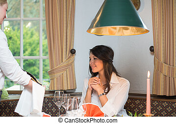 Waitress showing wine bottle to female client - Young...