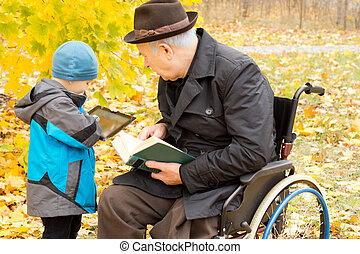 Young boy showing his grandfather his tablet - Young boy...
