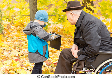 Little boy showing his grandfather his tablet - Little boy...