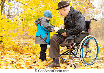 Young child with his disabled grandfather, who has one leg...