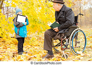 Youngster showing a disabled man a tablet-pc screen as the...