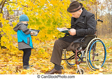 Small boy with his handicapped grandfather outdoors in a...