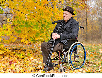 Thoughtful senior amputee sitting outdoors in his wheelchair...