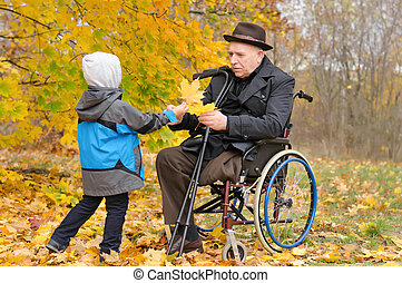 Young child giving an elderly man autumn leaves - Young...