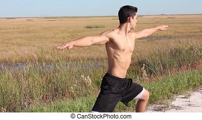 Young man doing yoga. Peaceful environment. Outdoors