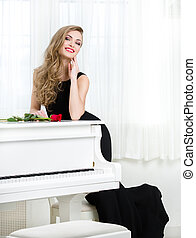Full length portrait of woman standing near the piano -...