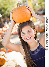 Preteen Girl Portrait at the Pumpkin Patch in a Rustic...