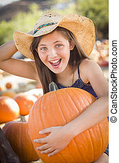 Preteen Girl Holding A Large Pumpkin at the Pumpkin Patch -...