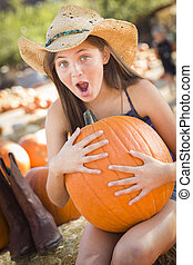 Preteen Girl Holding A Large Pumpkin at the Pumpkin Patch in...