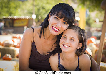 Attractive Mother and Daughter Portrait at the Pumpkin Patch...