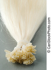 Blond hair extensions shot on a dark background