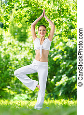 Full-length portrait of sportswoman exercising in park...
