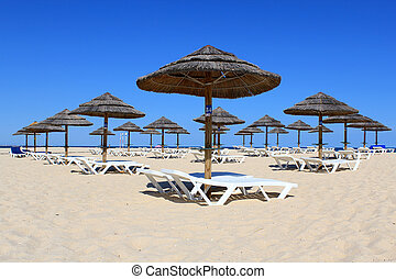 Parasol and sun loungers on the beach sand, Algarve -...