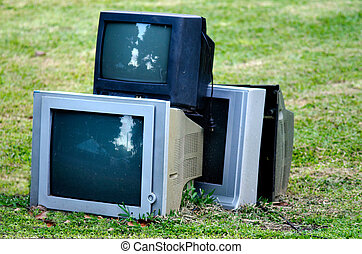 Broken television stacked for disposal outdoor.