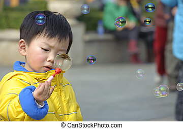 child blowing soap bubbles
