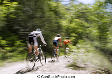 Mountain Bikers - Blurred panning shot of three mountain...