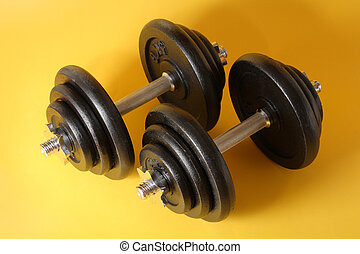 Dumbells - A Pair of iron dumbells on a yellow surface