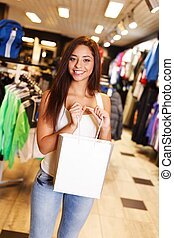 Beautiful happy brunette girl with shopping bag in a sport...