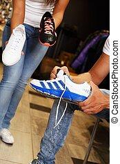 People choosing sports footwear in sport outlet
