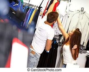 Happy young couple with shopping bag in choosing sportswear...