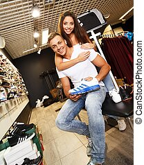 Young beautiful couple choosing sports footwear in a sport outlet