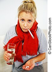 Sick young blond woman with pills, thermometer, and glass of...