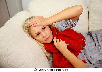 Sick young woman with thermometer lying on sofa at home