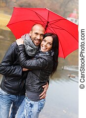 Happy middle-aged couple with umbrella outdoors on beautiful...