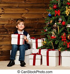 Little boy opening gift box under christmas tree in wooden...