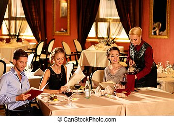 Group of young friends with menus choosing in a luxury...