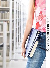 Student at library - A shot of a student carrying books at...