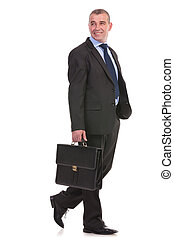 business man walks with briefcase and looks away - full...