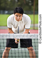 Asian tennis player - A young sporty asian male playing...