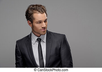Handsome young businessman. Portrait of handsome young businessmen looking away while standing isolated on grey