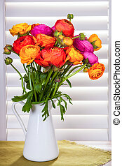 Flowers in a vase with sun light coming out of window blinds...