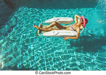 Blonde girl relaxing in pool