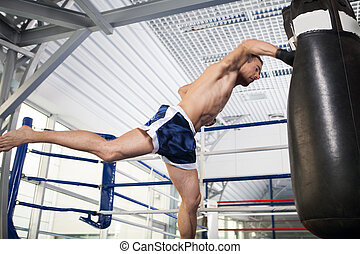 Boxer. Aggressive young kickboxer training at the punching...