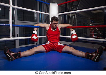 Defeated boxer Frustrated young boxer sitting on the boxing...