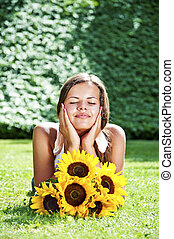 Young woman with a bouquet of sunflowers in the field closed...
