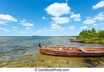 Summer lake view with wooden boats. - Summer lake view with...