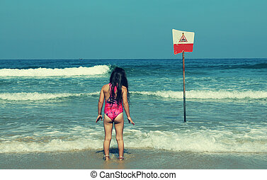 little girl on blue sea shore in summer vacation